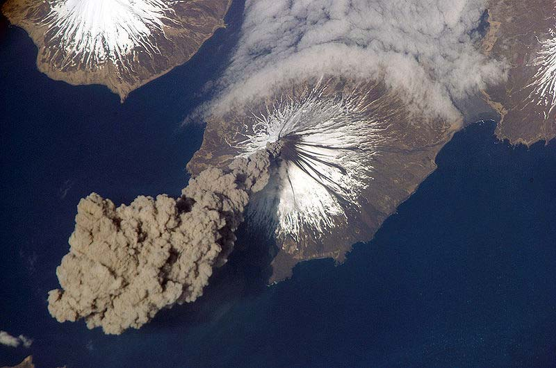This amazing photo shows a volcanic eruption as seen from space. A giant plume of smoke bellows out from the ice capped volcanic crater.