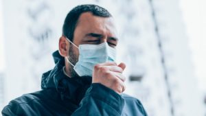 man wearing a mask and coughing
