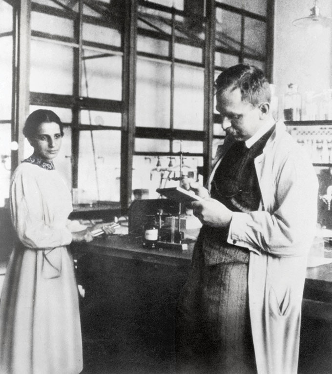 Lise Meitner stands next to a lab table and Otto Hahn holds a clipboard