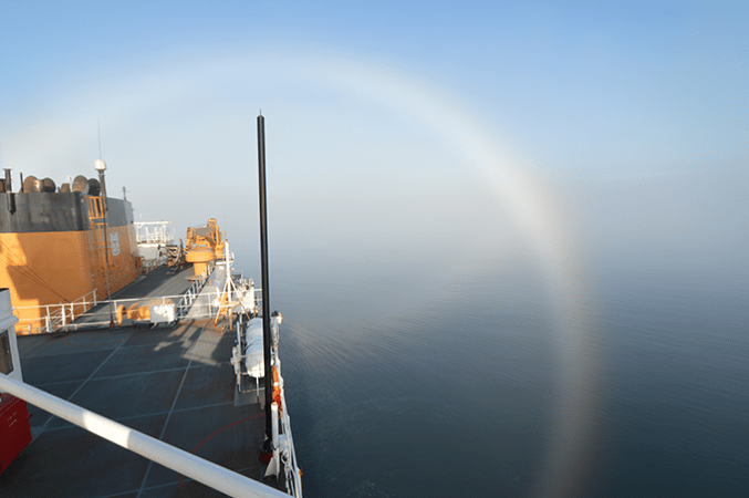 a fogbow from atop an icebreaker arcing below the horizon