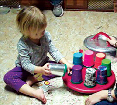 a photo of a child doing a spin-the-pots task