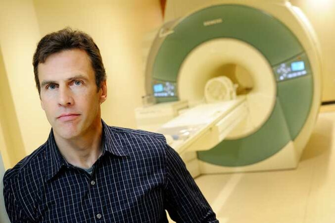 a photo of a man standing in front of a fMRI machine
