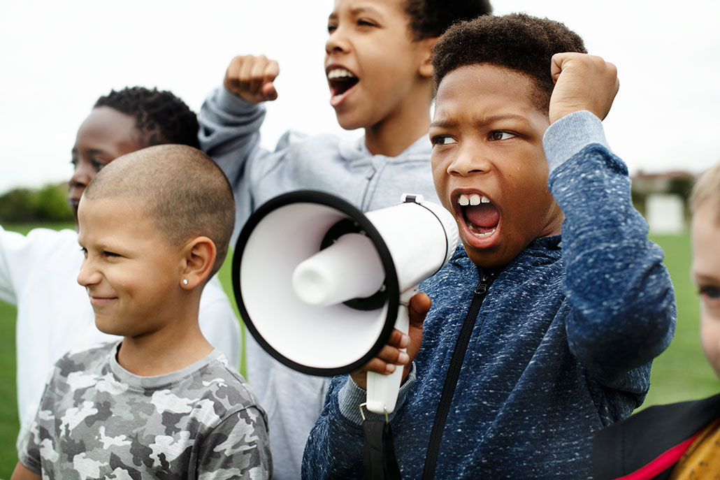 a photo of a young Black teen shouting into a megaphone at a protest