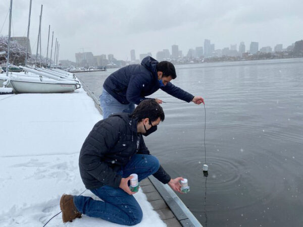 two men placing a sensor in a river on a snowy day