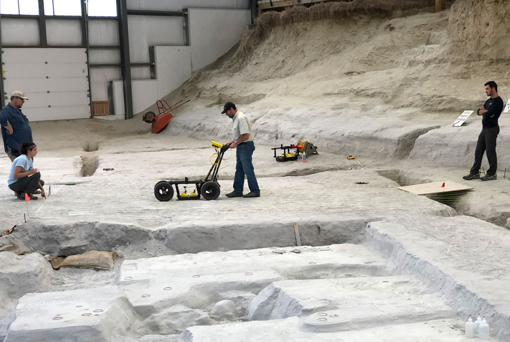 Researchers pushing a ground-penetrating radar machine over the ground.