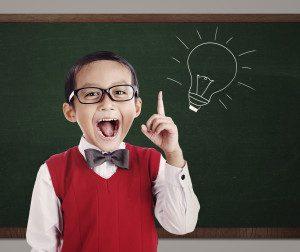 Portrait of male elementary school student with lightbulb picture on blackboard