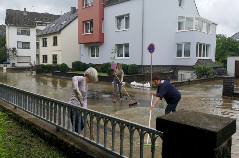 Mayen residents in Germany try to clean flooded streets on July 15, 2021 (AFP - Michelle FITZPATRICK)