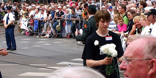 Jongen deelt witte anjers uit op Veteranendag. Ze staan symbool voor waardering voor veteranen. Foto: Roel Wijnants.