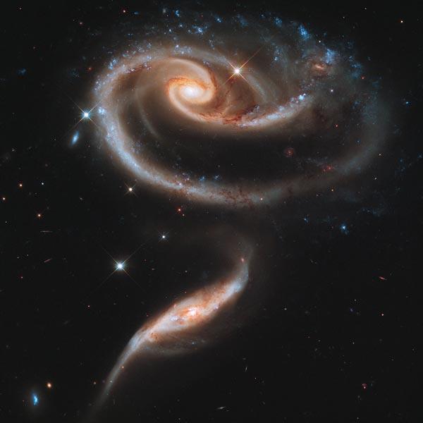 Op deze foto ziet u twee sterrenstelsels die elkaar overduidelijk beïnvloeden. Wetenschappers denken dat het kleine sterrenstelsel ooit door het grote sterrenstelsel heen is gereisd. Foto: NASA / ESA / Hubble Heritage Team (STScI / AURA).