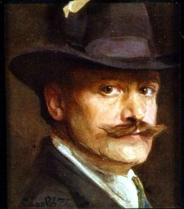 Een zelfportret van Philip Alexius de Laszlo.  Deze hofschilder zat twee jaar lang gevangen omdat hij werd verdacht van spionage door het publiek. Jaren later is zijn reputatie weer hersteld en bevindt hij zich weer in koninklijke kringen. Zo maakte hij onder andere een portret van de toen nog prinses Elizabeth, nu de koningin van Groot-Brittannië. Bron: Wikimedia Commons.