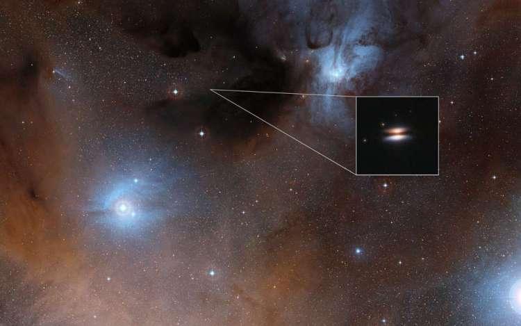 De protoplanetaire schijf van de jonge ster 2MASS J16281370-2431391 zien we bijna van opzij. De schijf heeft dan ook een toepasselijke bijnaam: Vliegende Schotel. Afbeelding: Digitized Sky Survey 2 / NASA / ESA.