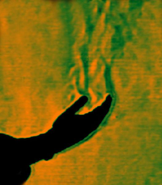 Fotografia Schlieren dell'aria riscaldata da una mano umana che sale per convezione (immagine di wikimedia).