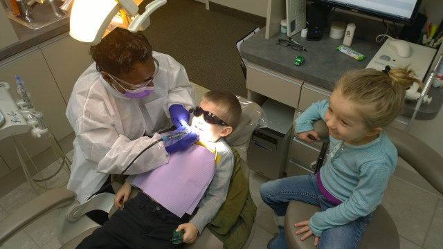 My son's big sister sitting with him at the dentist to make sure he was OK.