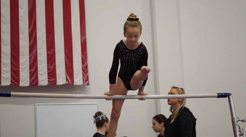 Practicing her mill circle on bars at a gymnastics meet