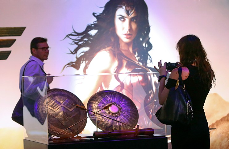 """A fan takes a picture of the Amazon Army Shield, Queen's Guard Shield, and Amazon Army Quiver and Arrows from the highly-anticipated film """"Wonder Woman"""" at the Warner Bros. Consumer Products booth at Licensing Expo 2016 on Tuesday, June 21, 2016 in Las Vegas. (Photo by Bizuayehu Tesfaye/Invision for Warner Bros. Consumer Products/AP Images)"""