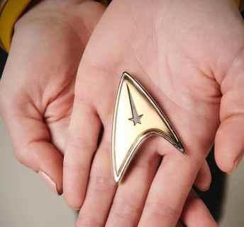 Rebecca Romijn holding starfleet insignia