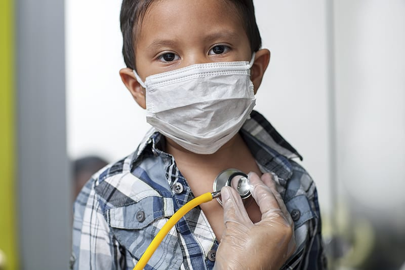 Child wearing a medical mask to prevent spread of virus is getting a heart screening with stethoscope placed on chest.