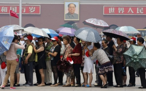 Tourists holding umbrellas visit Tiananmen Square in Beijing. Photo: Reuters