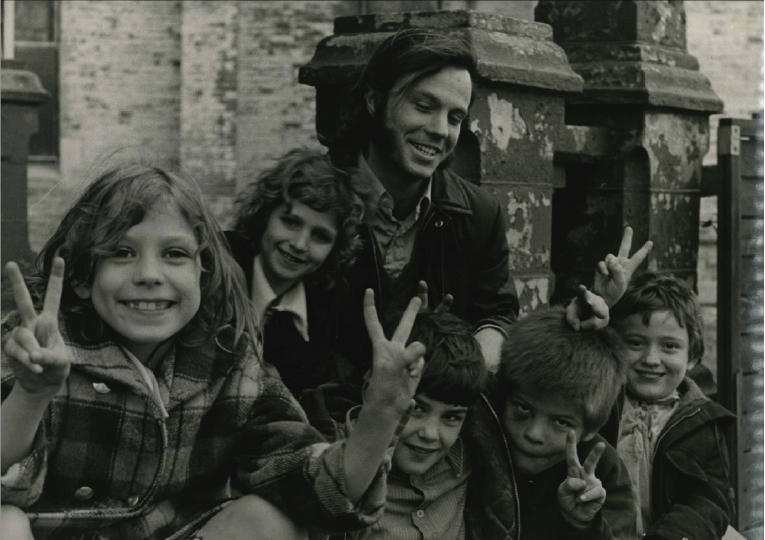 Steve in his early years, posing with a group of kids.