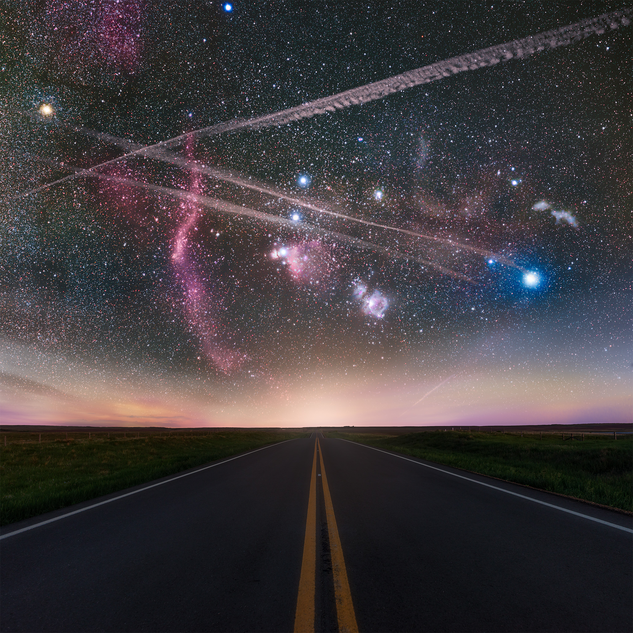 Landscape astrophotography in Saskatchewan of the Orion constellation over a road