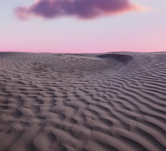 A landscape photograph of the Great Sandhills of Saskatchewan. Sand dunes and a cloud