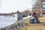 People enjoying the sun along the Ume River.