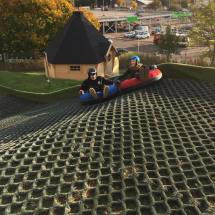 Two participants going down dry ski slope in giant inner tubes, smiling