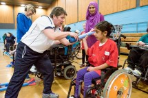 Shona Malcolm from Scottish Athletics demonstrating javelin hold to girl using wheelchair