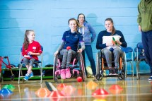 Shelby Watson demonstrating boccia throw to two participants