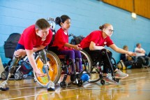 Two wheelchair users and double amputee practicing boccia throws
