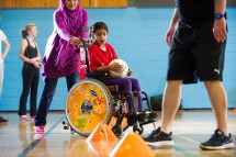 Wheelchair user practicing football drill
