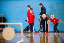 Two standing participants practicing boccia throws with coach