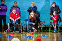Three girls, two using wheelchairs and one seated, practicing boccia throws