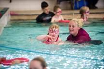 Young girl in pool receiving swimming coaching
