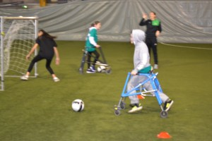 Two participants using walking frames playing football with coaches