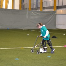 Girl with walking frame dribbling football on pitch
