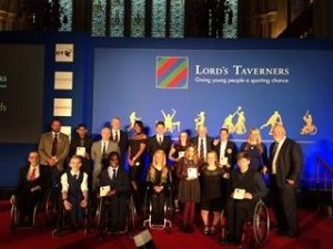 Group photo of award winners including Josh Manson in front of Lord's Taverners screen