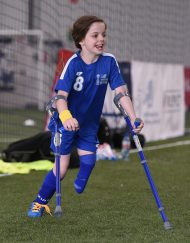 Keeley playing football on crutches