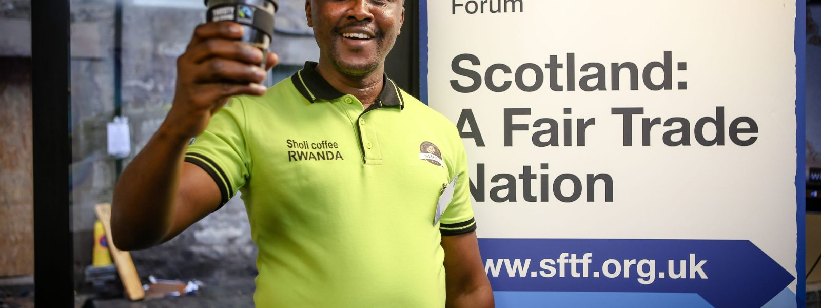 A man holding a Fair Trade cup in front of a Fair Trade banner.