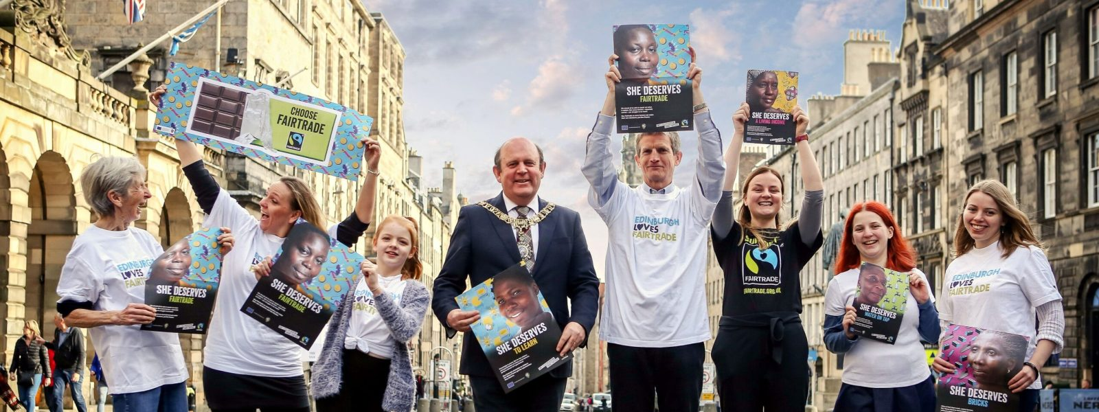 A group of campaigners standing in a line in Edinburgh holding Fair Trade posters