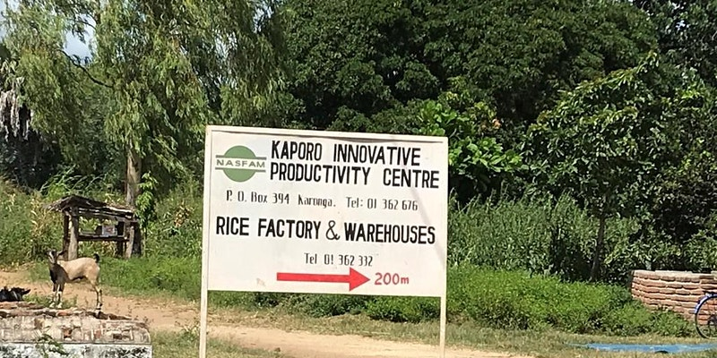 White sign directing to the Kaporo Initiative Productivity Centre in Malawi.