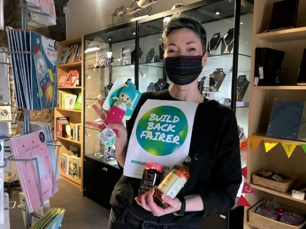 Member of staff at One World Shop holding Build Back Fairer sign, Fair trade toy and Fair Trade sauces