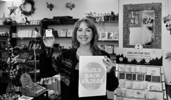 A woman in a Fair Trade gift shop holding a Build Back Fairer sign and a Fair Trade necklace