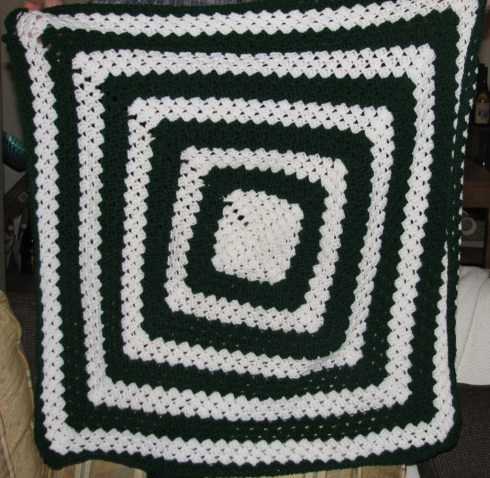 A green and white crocheted throw of concentric squares that tilt a bit with each round