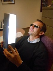 """A man in shades holds a """"happy light"""" to his face"""