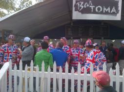 A group of men at a PGA tournament wear hats and jumpsuits resembling the British Flag