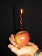 A lit squiggly candle stuck in an apple resting on the palm of a hand
