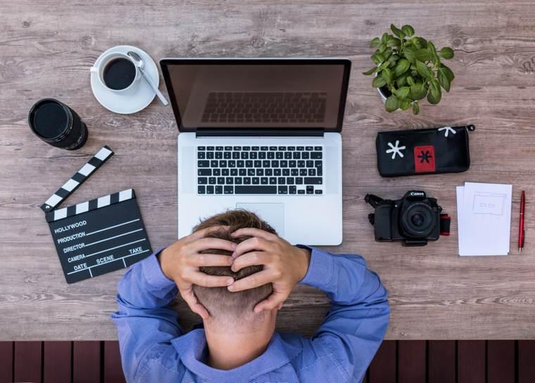 Il blocco dello scrittore: uno scrittore davanti al computer con le mani nei capelli.