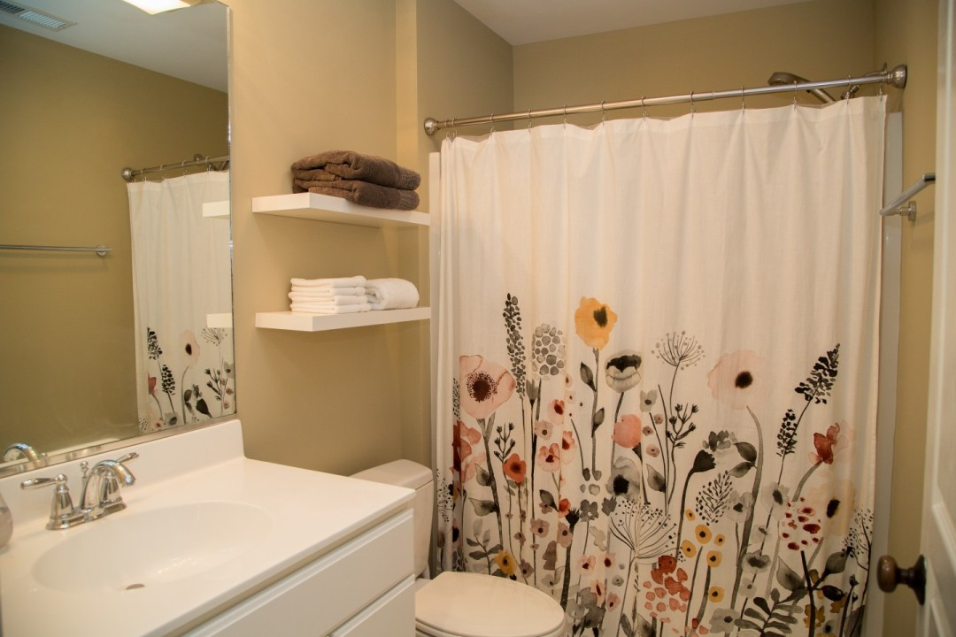 Bathroom with Beige Wall Paint, White Vanity and Flower Shower Curtain
