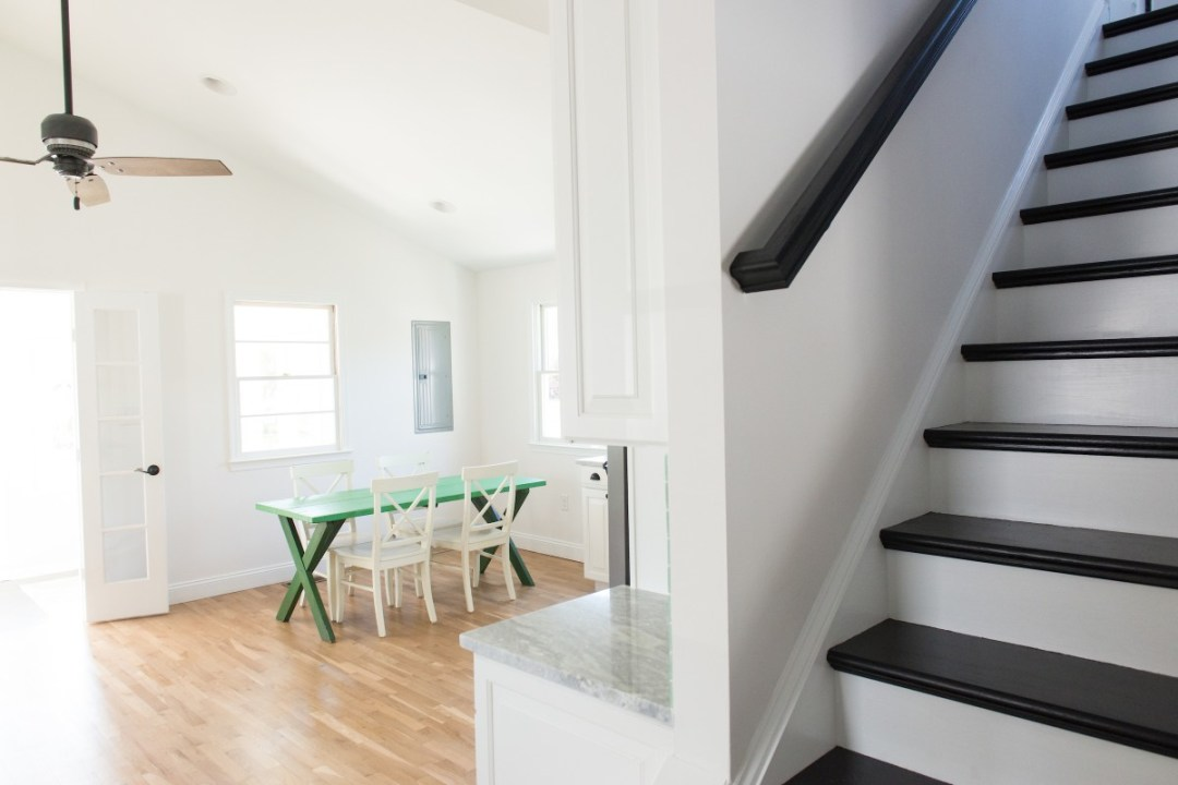 Kent Renovation Bethany Beach, DE Black and White Stairway with Black Railing, Green Dining Table and White Chairs